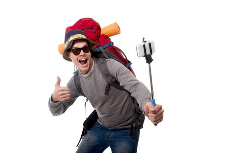 若い魅力的なバックパッカー観光撮影 selfie 棒運ぶバックパック旅行の準備ができてし、白い背景で隔離の休暇ルート冒険で写真します。