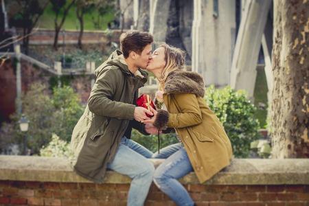 bacio: coppia in amore baciare sulla strada festeggiare San Valentino con ragazza riceve a forma di cuore box presente nel parco cittadino di fondo urbano Archivio Fotografico