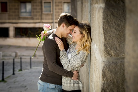 street love: candid portrait of beautiful European couple with rose in love kissing on street alley celebrating Valentines day with passion against stone wall on urban background Stock Photo