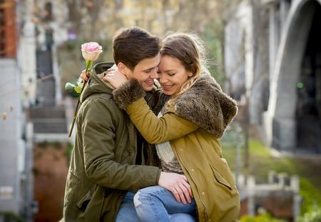 enamorados besandose: sincero retrato de la bella pareja Europea con la rosa en el amor bes�ndose en la calle celebrando el d�a de San Valent�n con la pasi�n que se sienta en parque de la ciudad en el invierno de fondo urbano