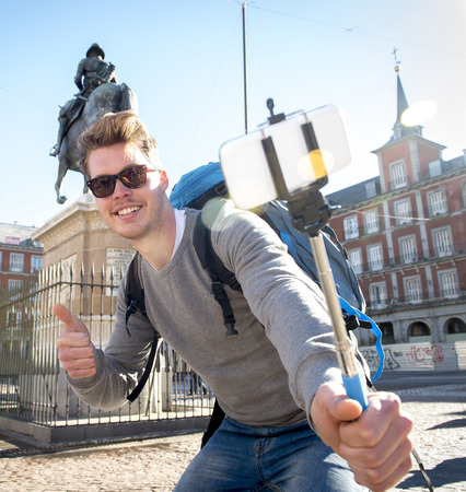 student travel: young attractive student backpacker tourist taking selfie photo with stick and mobile phone outdoors enjoying holidays travel destination in tourism and exploring concept
