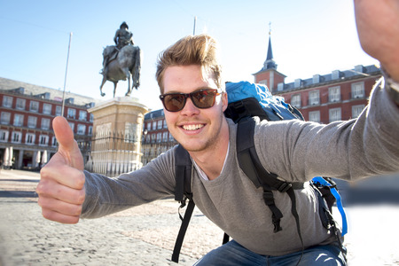 backpackers: young attractive student backpacker tourist taking selfie photo with mobile phone outdoors enjoying holidays travel destination in tourism and exploring concept Stock Photo