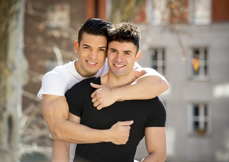 men body: young happy attractive gay men couple with strong fit body cuddling posing outdoors on street in sexual freedom and free homosexual love concept in urban background