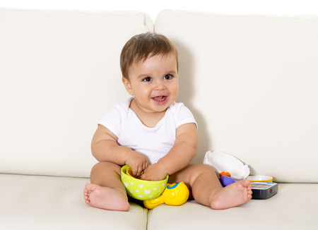 boy 12 year old: sweet cute little baby sitting on couch alone at home playing with toys happy and relaxed having fun smiling happy and laughing wearing white t-shirt and dippers