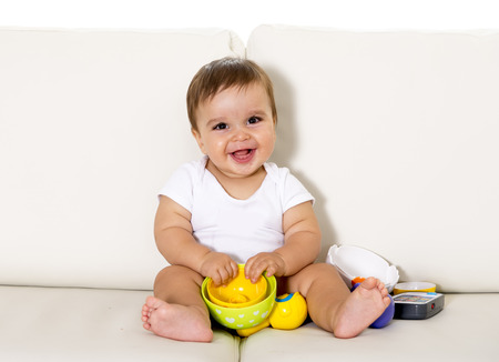 sweet cute little baby sitting on couch alone at home playing with toys happy and relaxed having fun smiling happy and laughing wearing white t-shirt and dippers