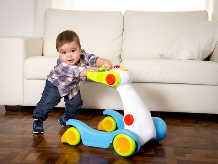 trying on: sweet little one year old boy walking alone with baby walker taking his first brave steps at home in living room excited and playful in childhood and growth concept Stock Photo