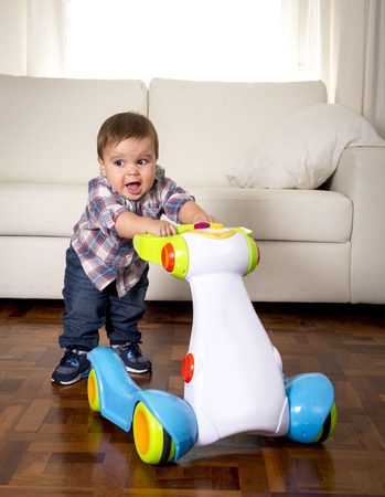 12 step: sweet little one year old boy walking alone with baby walker taking his first brave steps at home in living room excited and playful in childhood and growth concept Stock Photo