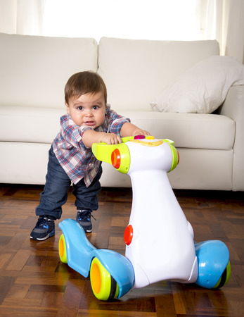 sweet little one year old boy walking alone with baby walker taking his first brave steps at home in living room excited and playful in childhood and growth concept Stock Photo