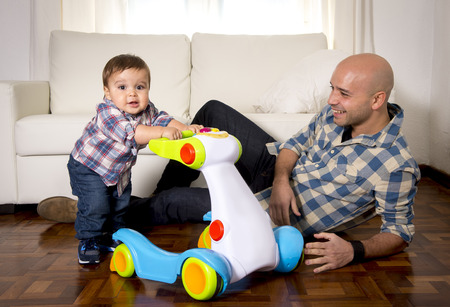 12 step: young happy father and little one year old son walking with baby walker taking his first brave steps at home in living room excited and playful in childhood and growth concept