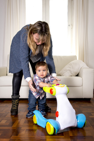 12 step: young mother and little one year old son walking with baby walker taking his first brave steps at home in living room excited and playful in childhood and growth concept