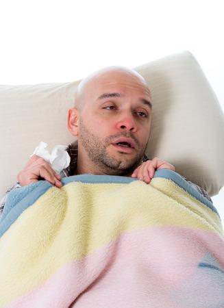gripe: joven hombre enfermo y enfermo en el tejido que sostiene la cama limpieza nariz mocosa tener sensaci�n temperatura mala infectados por el virus de gripe de invierno en la gripe y la atenci�n sanitaria de la influenza concepto