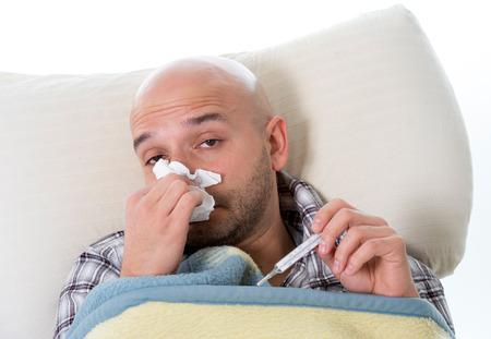 chory: Młody człowiek chory i chory w łóżku trzyma tkanki czyszczenia zasmarkany nos, mający poczucie temperatury źle zainfekowany przez wirusa grypę w zimowej grypy i grypy koncepcji opieki zdrowotnej