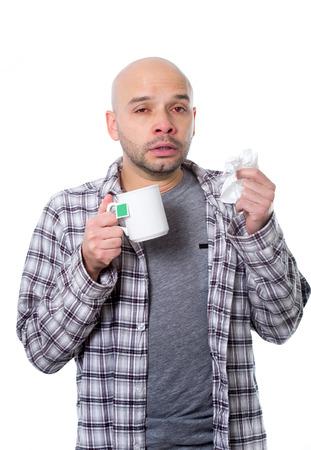 gripe: hombre enfermo joven infectada por el virus de gripe de invierno sensaci�n unwell estornudos taza para beber nariz de t� temperatura gripe sufrimiento en concepto fr�o y la atenci�n sanitaria de la influenza