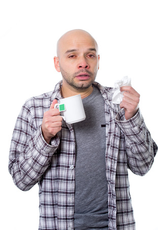snotty: young sick man infected by winter grippe virus feeling unwell sneezing nose drinking cup of tea suffering flu temperature in cold and influenza health care concept