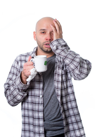 snotty: young sick man infected by winter grippe virus feeling unwell holding cup of tea suffering flu, headache and temperature in cold and influenza health care concept Stock Photo