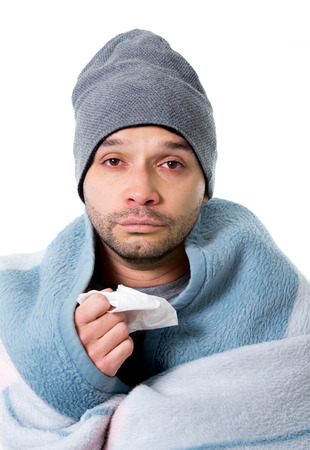 grippe: young sick and ill man in bed holding tissue cleaning snotty nose having temperature feeling bad infected by winter grippe virus in flu and influenza health care concept