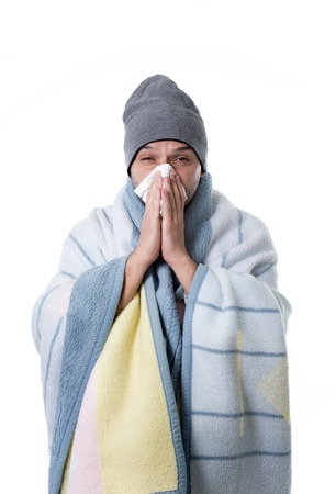 snotty: young sick and ill man in bed holding tissue cleaning snotty nose having temperature feeling bad infected by winter grippe virus in flu and influenza health care concept