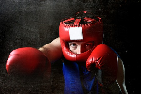 headgear: amateur boxer man training shadow boxing with red fighting gloves and headgear protection throwing angry right punch attack isolated on grunge dirty background Stock Photo