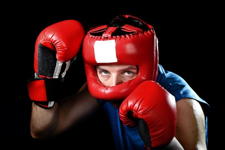 headgear: amateur boxer man training shadow boxing with red fighting gloves and headgear protection in defense stance isolated on black  background