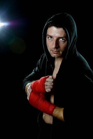 boxing tape: young man in boxing hoodie jumper with hood on head wearing hand and wrist wrapped ready for fighting posing isolated on black background with angry face expression