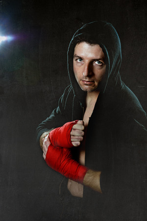 young man in boxing hoodie jumper with hood on head wearing hand and wrist wrapped ready for fighting posing isolated on black grunge dirty background with angry face expression