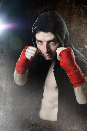boxing tape: young man in boxing hoodie jumper with hood on head wearing hand and wrist wrapped posing on boxer stance in grunge dirty background with angry face expression