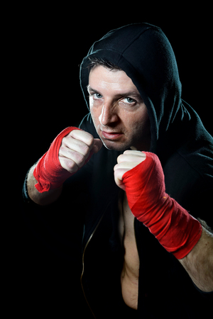 boxing tape: young man in boxing hoodie jumper with hood on head wearing hand and wrist wrapped posing on boxer stance in black background with angry face expression