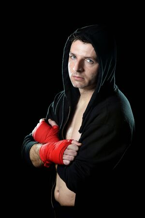 boxing tape: young man in boxing hoodie jumper with hood on head wearing hand and wrist wrapped ready for fighting posing isolated on black grunge dirty background with angry face expression