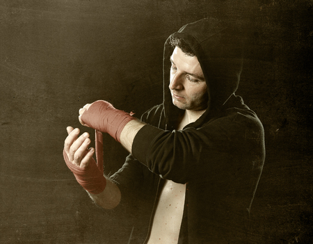 boxing tape: young man in boxing hoodie jumper with hood on head wrapping hands and wrists getting ready for fighting posing concentrated isolated on black  background