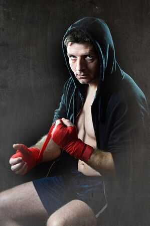 boxing tape: young man in boxing hoodie jumper with hood on head sitting wrapping hands and wrists getting ready for fighting posing concentrated isolated on black grunge dirty background Stock Photo