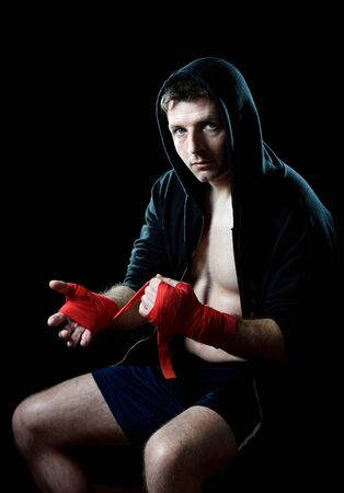 boxing tape: young man in boxing hoodie jumper with hood on head sitting wrapping hands and wrists getting ready for fighting posing concentrated isolated on black  background