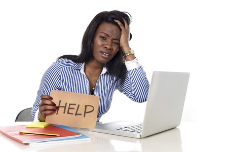 black African American ethnicity tired and frustrated woman working as secretary in stress at work office desk with computer laptop asking for help in business frustration and exploitation Stock Photo