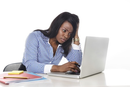 black African American ethnicity tired and frustrated woman working as secretary in stress at work office desk with computer laptop worried in business frustration concept