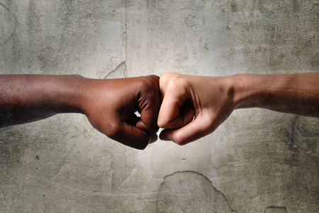 knuckles: black African American race female hand touching knuckles with white Caucasian woman in agreement partnership and cooperation multiracial diversity immigration concept