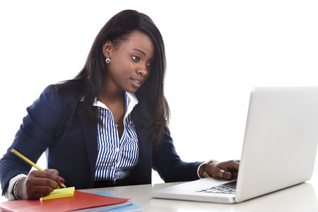 ethnicity: young attractive and efficient black ethnicity woman sitting at office computer laptop desk typing concentrated isolated on white background in business career and success concept