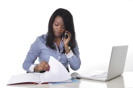 computer isolated: black African American ethnicity woman working hard as secretary in stress talking on mobile phone multitasking sitting at work office desk with computer laptop in women business concept Stock Photo