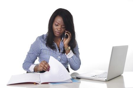 secretarias: negro africano americano mujer trabajando duro como secretario en el estrés hablando por teléfono móvil multitarea sentado en el escritorio de oficina de trabajo con el ordenador portátil en las mujeres concepto de negocio