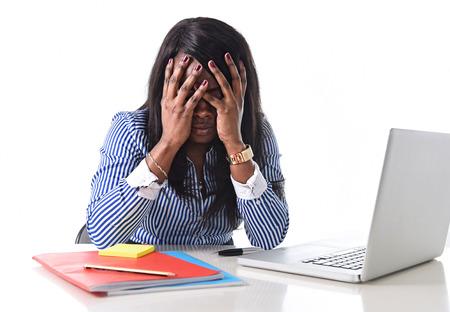 depresi�n: negro etnia afroamericana deprimida y frustrada mujer que trabaja como secretaria en el estr�s en el escritorio de oficina con el ordenador port�til desesperada en la depresi�n concepto de trabajo