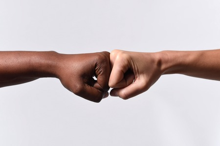 partnership: black African American race female hand touching knuckles with white Caucasian woman in agreement partnership and cooperation multiracial diversity immigration concept