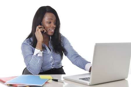 ethnicity: young attractive and black African American ethnicity woman working at computer laptop at office desk smiling happy talking on mobile phone in business success career concept Stock Photo