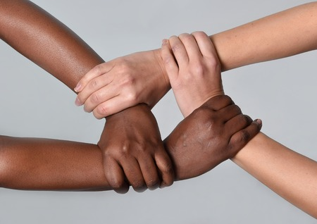 conceptual symbol: white Caucasian female hands and black African American holding together in world unity and racial love and understanding in tolerance and races diversity cooperation concept