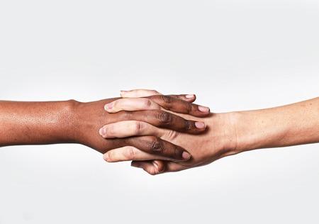 mujeres juntas: blancos caucásicos manos femeninas y dedos afroamericanas negras que sostienen juntos en la unidad del mundo y el amor racial y la comprensión en la tolerancia y razas concepto cooperación diversidad