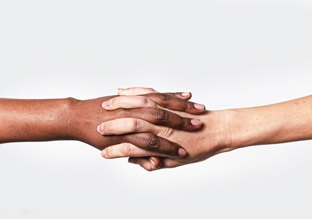 white Caucasian female hands and black African American holding fingers together in world unity and racial love and understanding in tolerance and races diversity cooperation concept Stock Photo