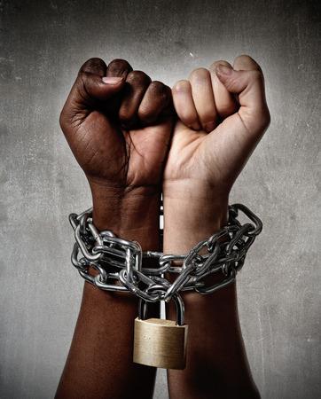 racismo: mano de raza blanca encadenado con cadena de hierro y encerrado junto con el origen étnico femenino negro alrededor de las muñecas en la convivencia, el respeto y la comprensión multirracial concepto