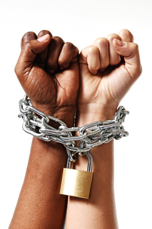 lock and chain: white Caucasian hand chained with iron chain and locked together with black ethnicity female around wrists in togetherness, multiracial respect and understanding concept