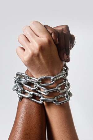 white Caucasian hand chained with iron chain and locked together with black ethnicity female around wrists in togetherness, multiracial respect and understanding concept