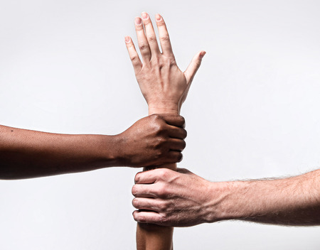 anti racist: black African American and Caucasian hands holding together white skin arm in world unity and racial love and understanding in tolerance and races diversity cooperation concept Stock Photo