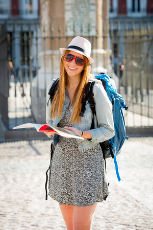 tourist guide: young happy attractive exchange student girl having fun in town visiting Madrid city reading tourist guide book having fun outdoors in tourism and travel vacation concept