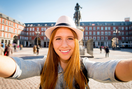 young beautiful tourist woman visiting Europe in holidays exchange students and taking selfie picture  in town smiling happy on sunny day in travel and vacation concept