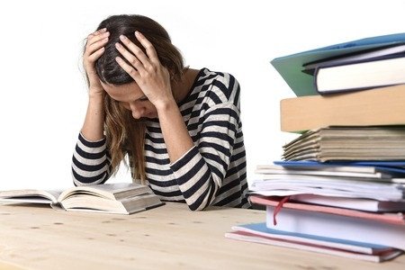 young stressed student girl studying pile of books on library desk preparing MBA test or exam in stress feeling tired and overwhelmed in youth education concept